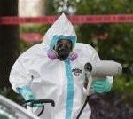 Hazmat worker cleans outside the apartment of the latest Ebola victim.