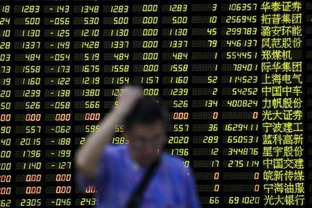 An investor stands in front of an electronic board showing stock information at a brokerage house in Shanghai, China, August 24, 2015.